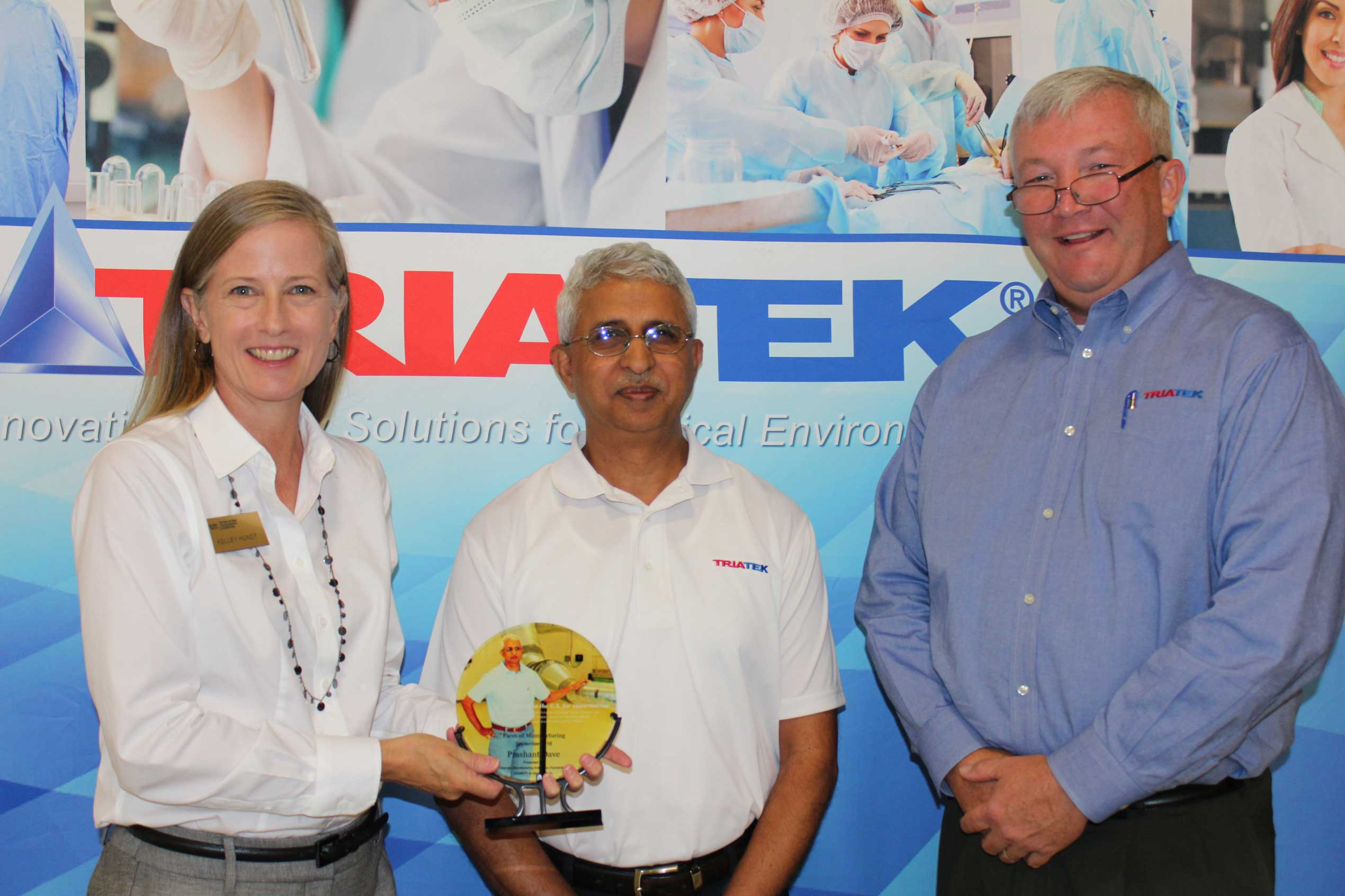 Kelley Hundt (left) is pictured with Prashant Dave and Triatek's CEO Jim Hall as she presents the award